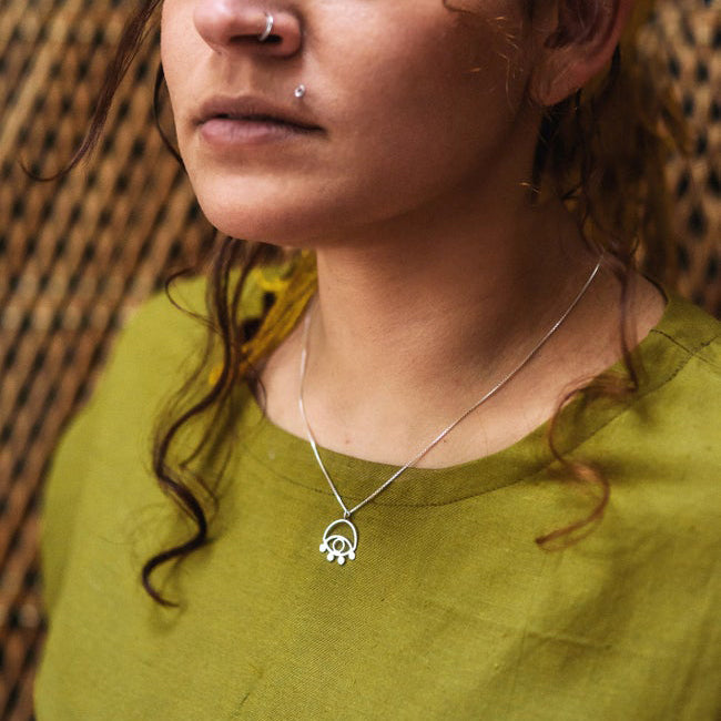 Lima Lima ecosilver eye necklace being worn by a model in a green linen top.