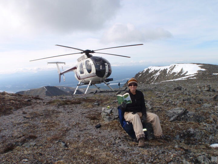 "Leigh reading to Beth in Alaska, ""My passenger snapped a pic of me in my rugged gear. I was working in a place with no cell service but checked my phone on this mountain top landing and actually had 2 bars so I called Mom for our daily reading. Otherwise I had to use the satellite system set up back at camp."""