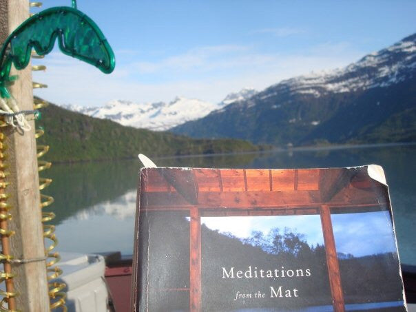 "Leigh reading ""Meditations from the Mat, Daily Reflections on the Path of Yoga"", by Rolf Gates while boat camping in Alaska and straining for cell service."