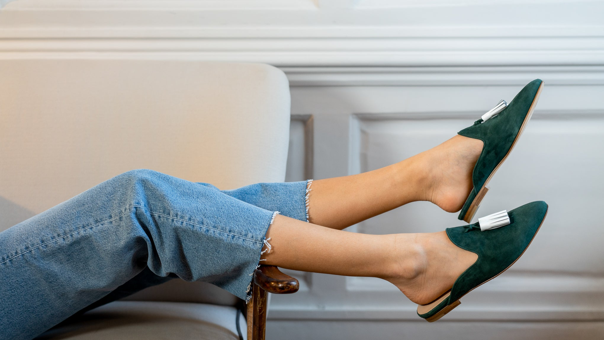 Woman relaxing with legs over the edge of a sofa wearing green slip-ons with white tassels sold by OA London