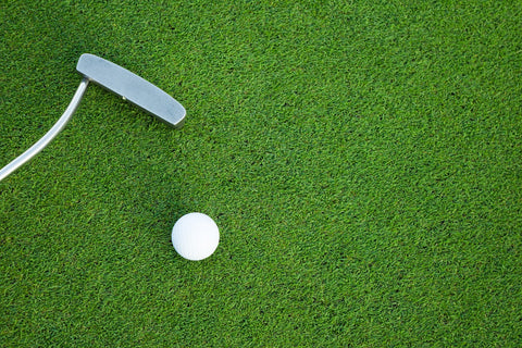 putter and golf ball on golf green