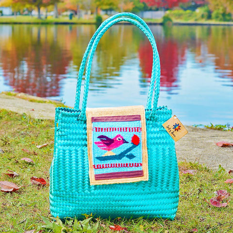 Fall setting with small mint colored Oaxaca straw woven tote bag with hand embroidered bird detail on flap enclosure