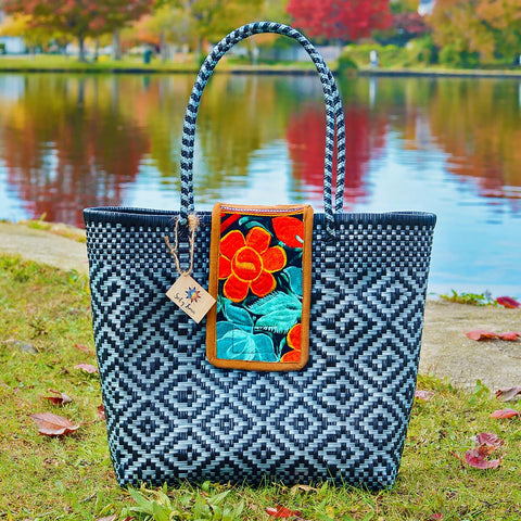 Fall setting with black and grey handwoven Oaxaca tote bag with embroidered flowers in orange and mint on flap enclosure
