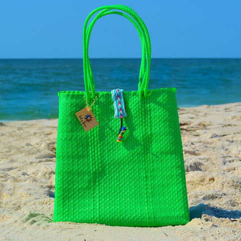 Beach scene with lime green handwoven Oaxaca tote bag with no worry doll on enclosure