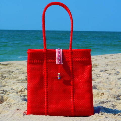 Beach scene with bright red handwoven Oaxaca tote bag with no worry doll on enclosure