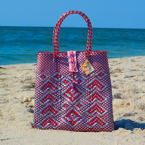 Beach scene with grey and red handwoven Oaxaca tote bag with no worry doll on enclosure