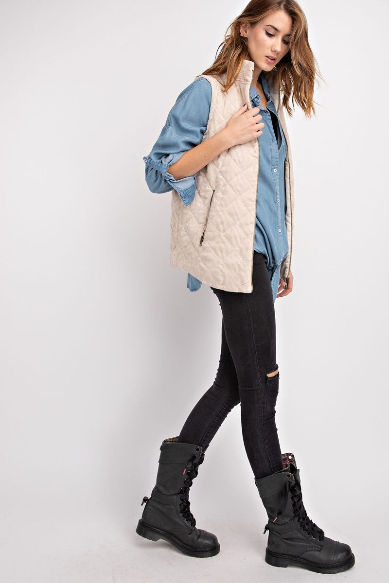 Woman wearing an oatmeal corduroy vest with pockets side view