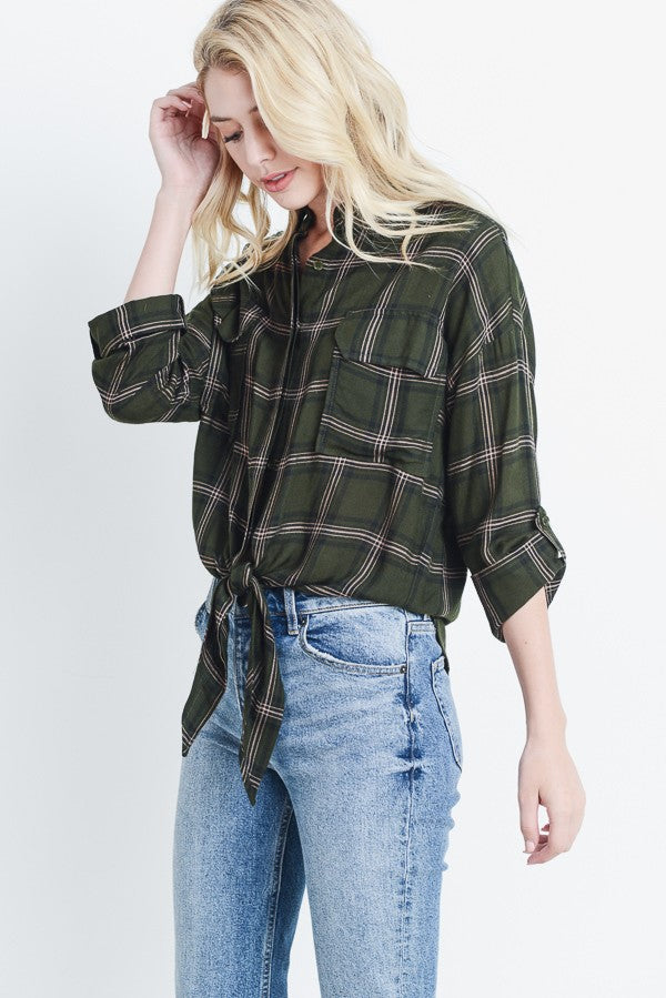 Blonde woman wearing a hunter green plaid button up shirt with a tie front detail