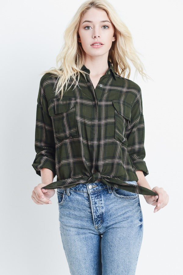 Blonde woman wearing a hunter green plaid button up shirt with a tie front detail front view