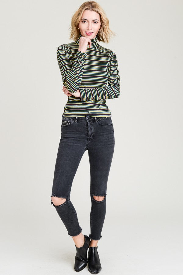 Woman wearing teal striped turtle neck top full body front view
