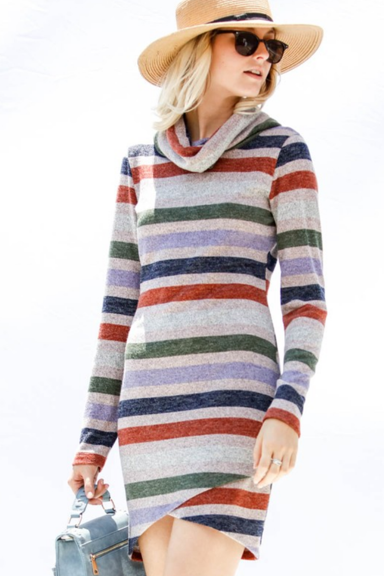 Woman wearing burgundy striped sweater dress with cowl neck looking to her left