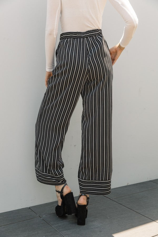 Woman wearing black and white striped wide leg pant with pockets back view