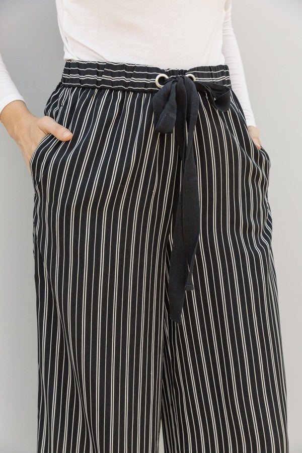 Woman wearing black and white striped wide leg pant with pockets close up view
