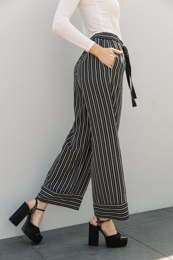 Woman wearing black and white striped wide leg pant with pockets side view