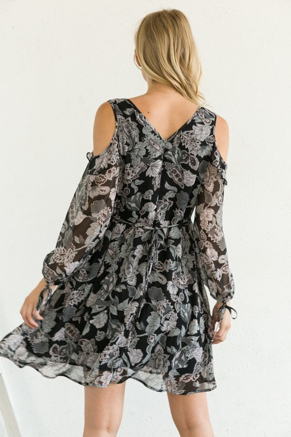 Blonde girl wearing cold shoulder grey printed dress with ruffle back view