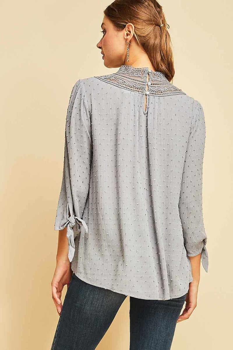 Woman wearing grey blouse with lace high neck back view