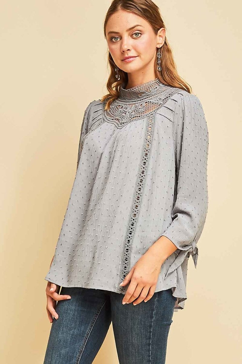 Woman wearing grey blouse with lace high neck front view