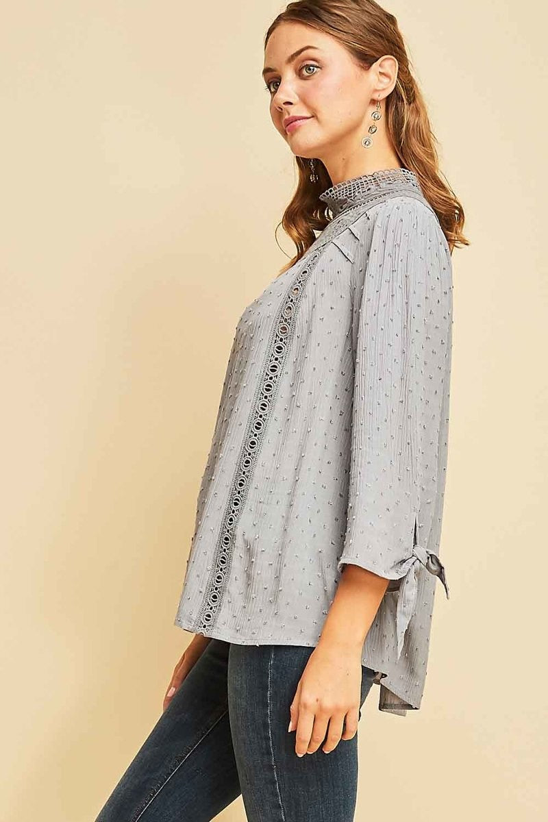 Woman wearing grey blouse with lace high neck side view