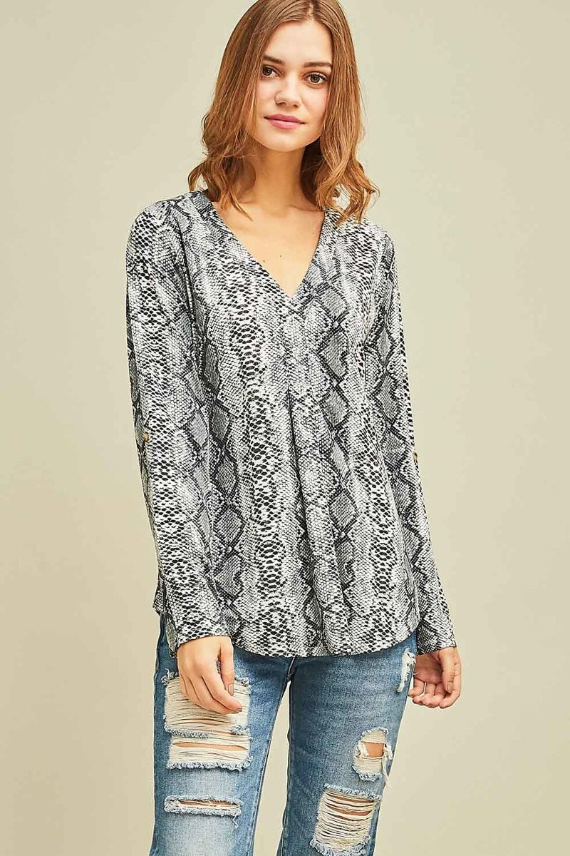 Woman wearing a grey snake print knit blouse