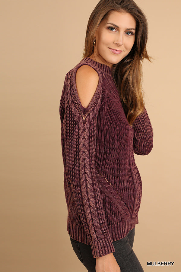 Brunette woman wearing a plum cold-shoulder cable knit sweater side view