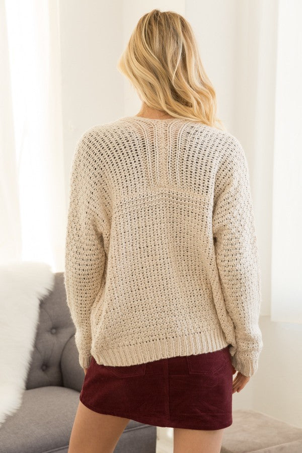 Blonde girl wearing a cream chunky knit cardigan with pockets back view