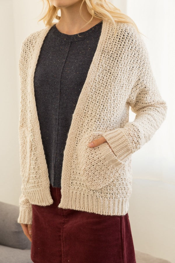 Blonde girl wearing a cream chunky knit cardigan with pockets close up view
