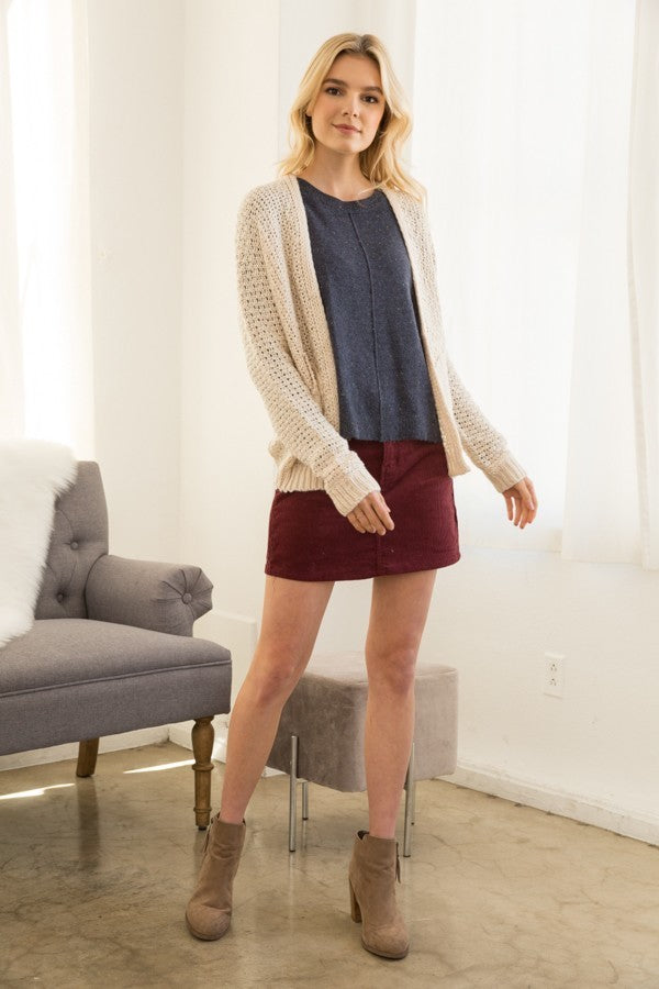 Blonde girl wearing a cream chunky knit cardigan with pockets full body view