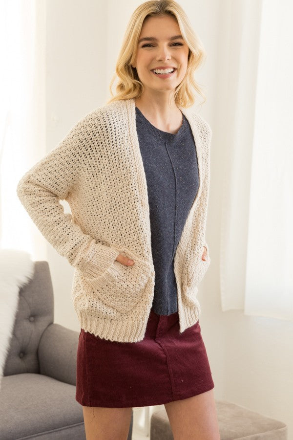 Blonde girl wearing a cream chunky knit cardigan with pockets