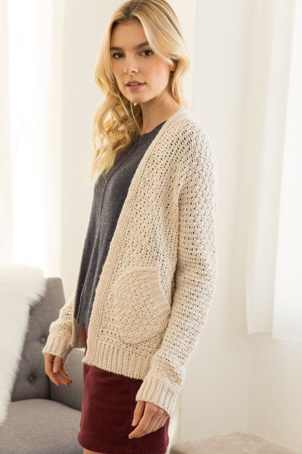 Blonde girl wearing a cream chunky knit cardigan with pockets side view