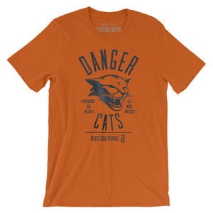 A retro bold, sarcastic graphic t-shirt in orange, featuring a mean cat image, with the words DANGER CATS, Vicious as heck—do not mess typography. From fashion brand Ruston/Bond, from wolfsaint.net