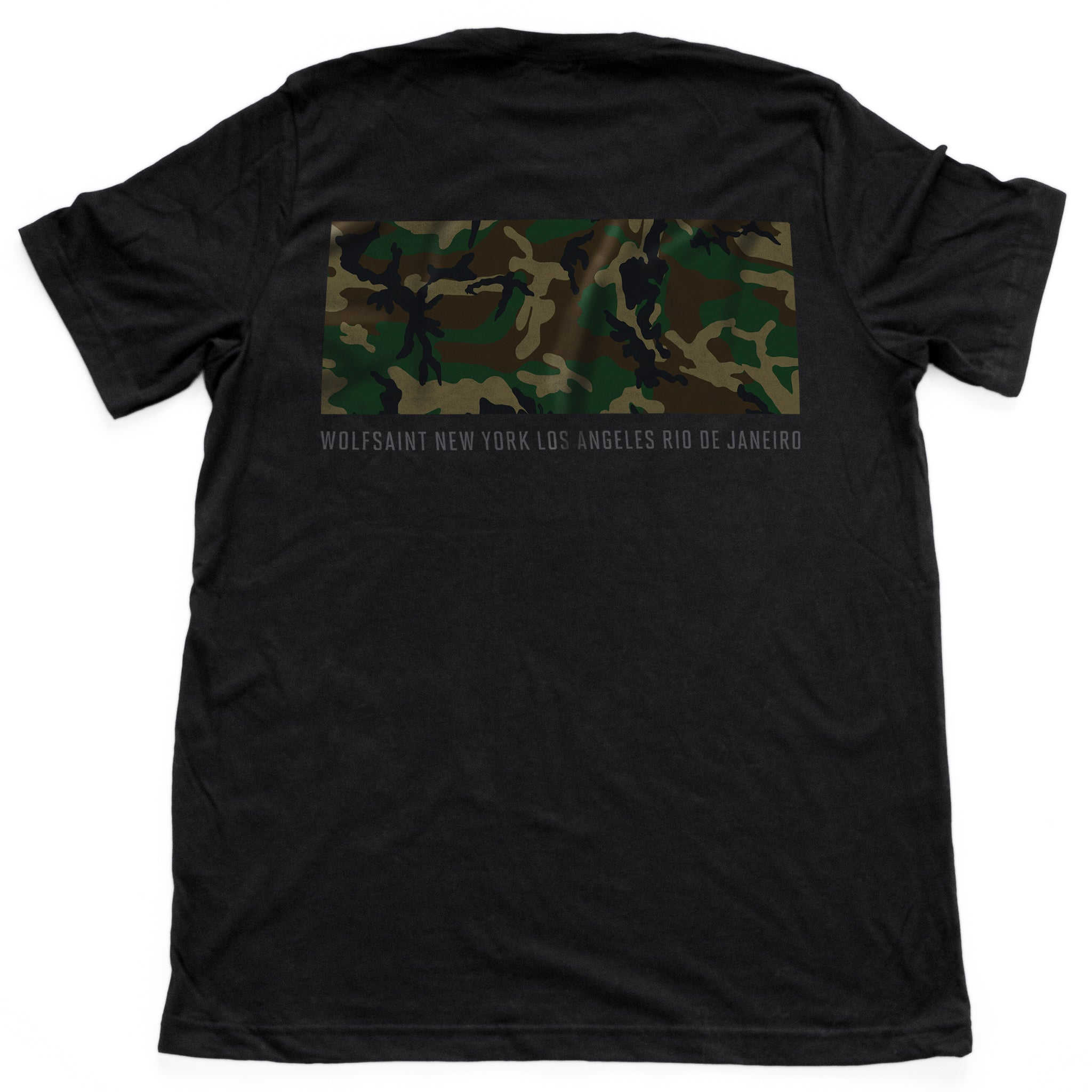 "The back side of a fashionable black t-shirt with a camo / camouflage panel on both sides. On the front there is also a Wolfsaint script logo within the camo panel; on the reverse are the Wolfsaint cities ""New York, Rio de Janeiro, Los Angeles"" listed innsmaller type below the camouflage. From Wolfsaint.net"
