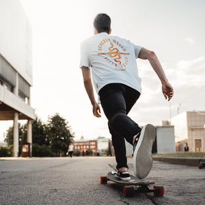 Skateboarder with a long board on the streets, wearing a Retro, vintage-inspired sarcastic fashion t-shirt with a graphic design snake (viper), for a fictional club or gang in Beverly Hills, California. From the brand Ruston/Bond.