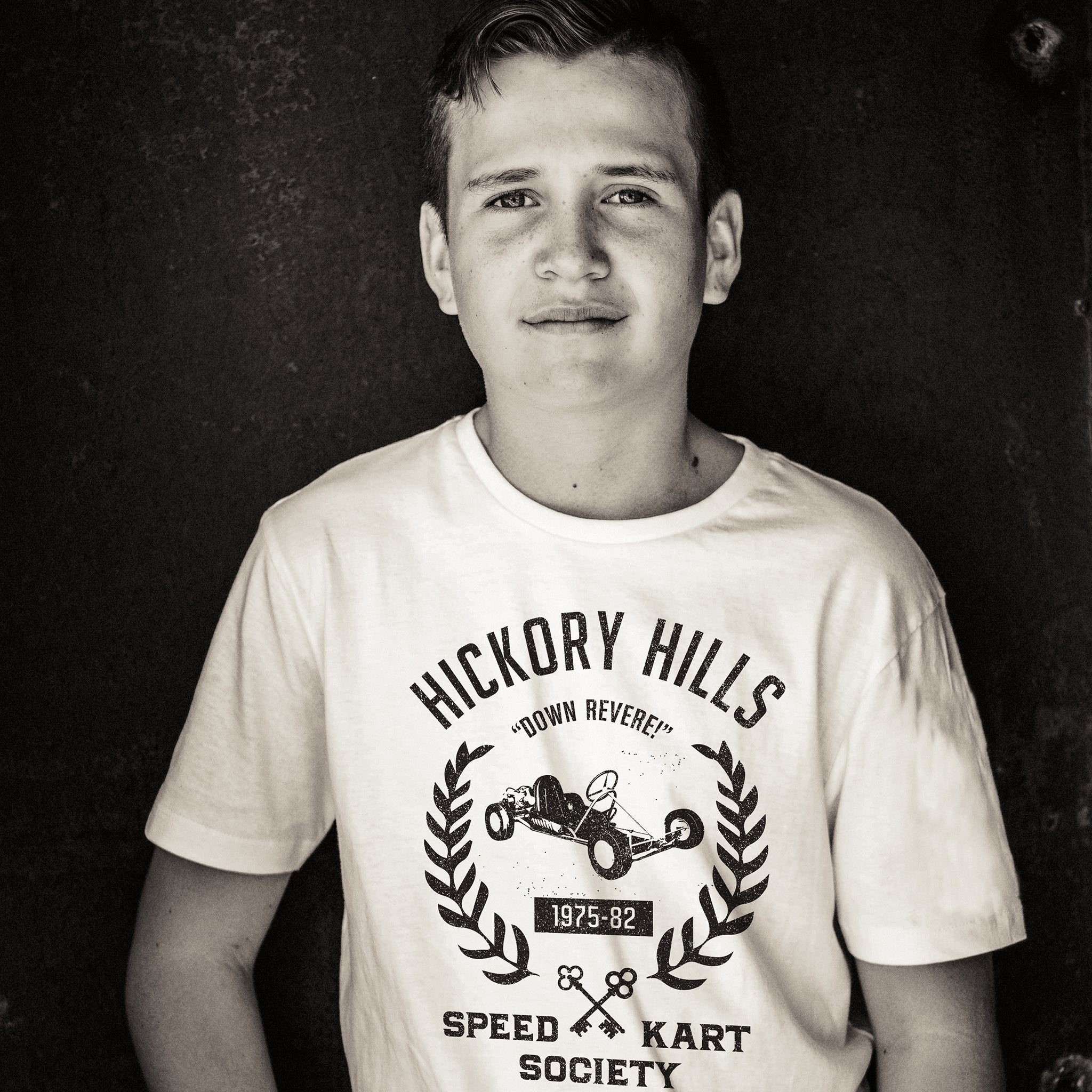 A young boy wears a 'vintage fiction,' retro t-shirt picturing a go-kart, promoting a small town racing league from 1975-1982 in Hockessin, Delaware. Inspired by the films of Wes Anderson. By fashion brand VNTG., from wolfsaint.net
