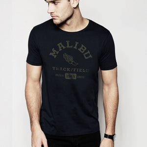 A male model in a studio wearing fashionable, vintage-inspired retro t-shirt in Classic Black, featuring a graphic representing a sarcastic and fictitious Malibu (California) Track and Field team. From wolfsaint.net