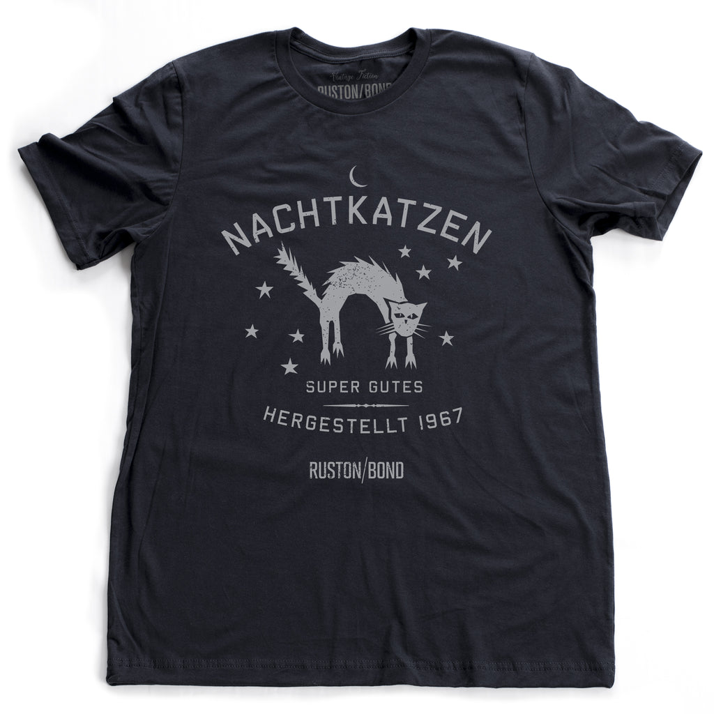 "A vintage-inspired retro design graphic t-shirt in classic Navy Blue, featuring the image of an arched cat among stars, and the German text ""NACHTKATZEN, Super Gutes"" — translating to ""Night Cats, super good"" and the year 1967, with the Ruston/Bond logo beneath. From wolfsaint.net"