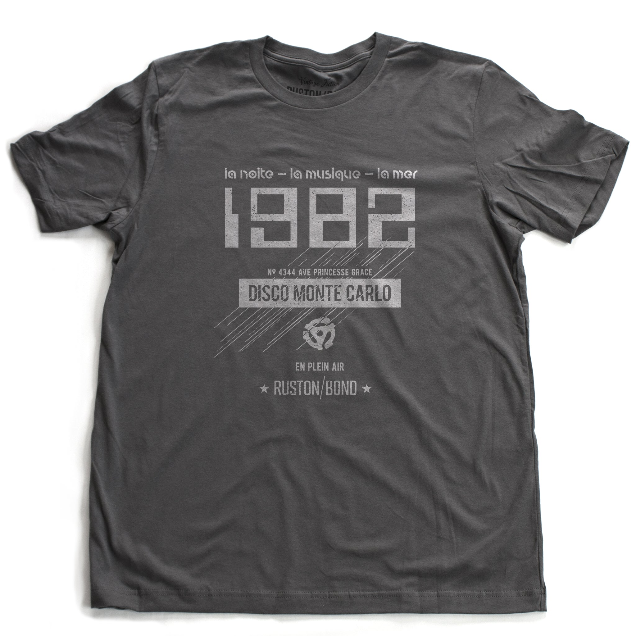 "A vintage-inspired t-shirt in asphalt gray, featuring retro digital font reading ""1982"" with French taglines and a 45 record adapter graphic, promoting a fictional Monte Carlo discotheque from the 1970s and 80s. By fashion brand Ruston/Bond, from wolfsaint.net"