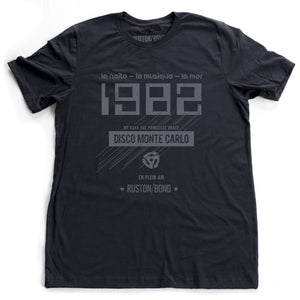 "A vintage-inspired t-shirt in navy, featuring retro digital font reading ""1982"" with French taglines and a 45 record adapter graphic, promoting a fictional Monte Carlo discotheque from the 1970s and 80s. By fashion brand Ruston/Bond, from wolfsaint.net"