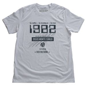 "A vintage-inspired t-shirt in white, featuring retro digital font reading ""1982"" with French taglines and a 45 record adapter graphic, promoting a fictional Monte Carlo discotheque from the 1970s and 80s. By fashion brand Ruston/Bond, from wolfsaint.net"