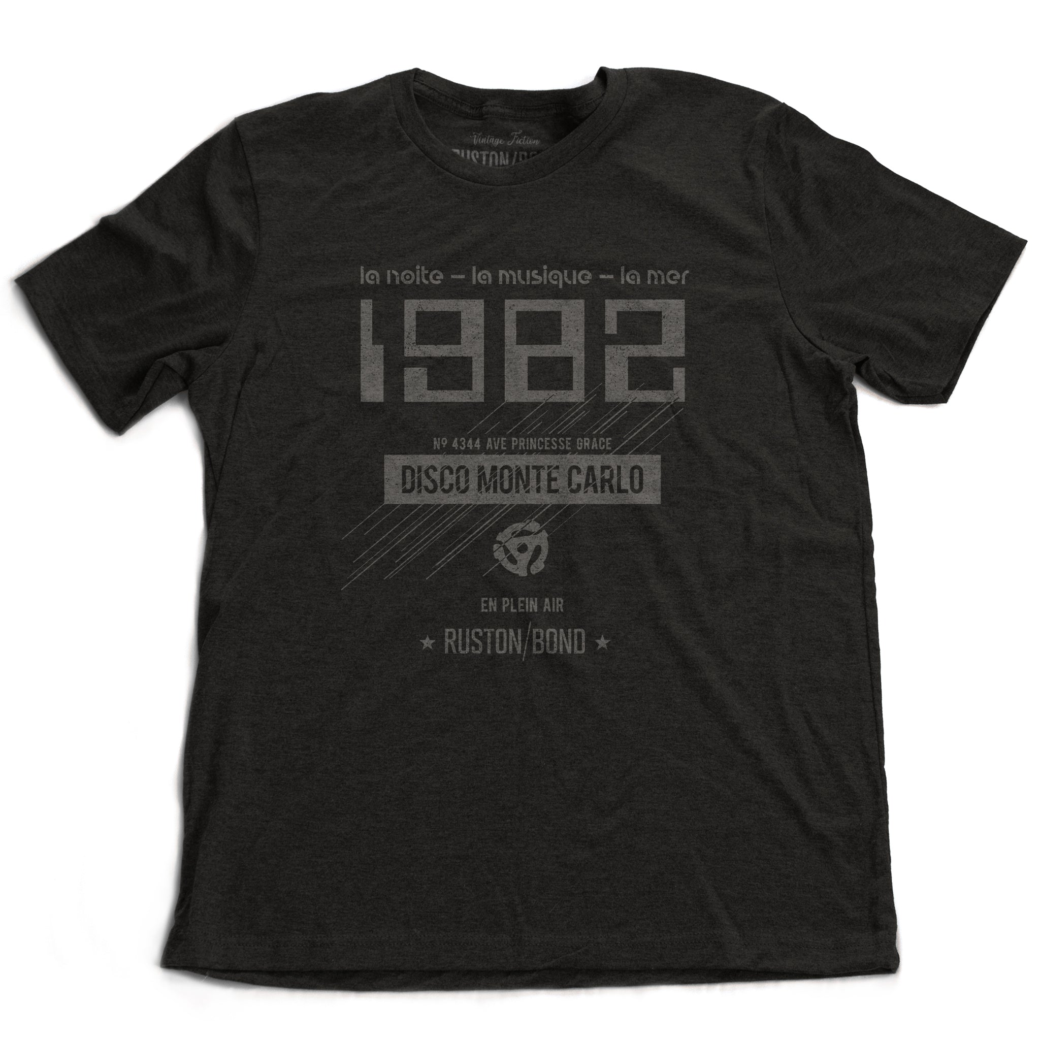 "A vintage-inspired t-shirt in classic black, featuring retro digital font reading ""1982"" with French taglines and a 45 record adapter graphic, promoting a fictional Monte Carlo discotheque from the 1970s and 80s. By fashion brand Ruston/Bond, from wolfsaint.net"