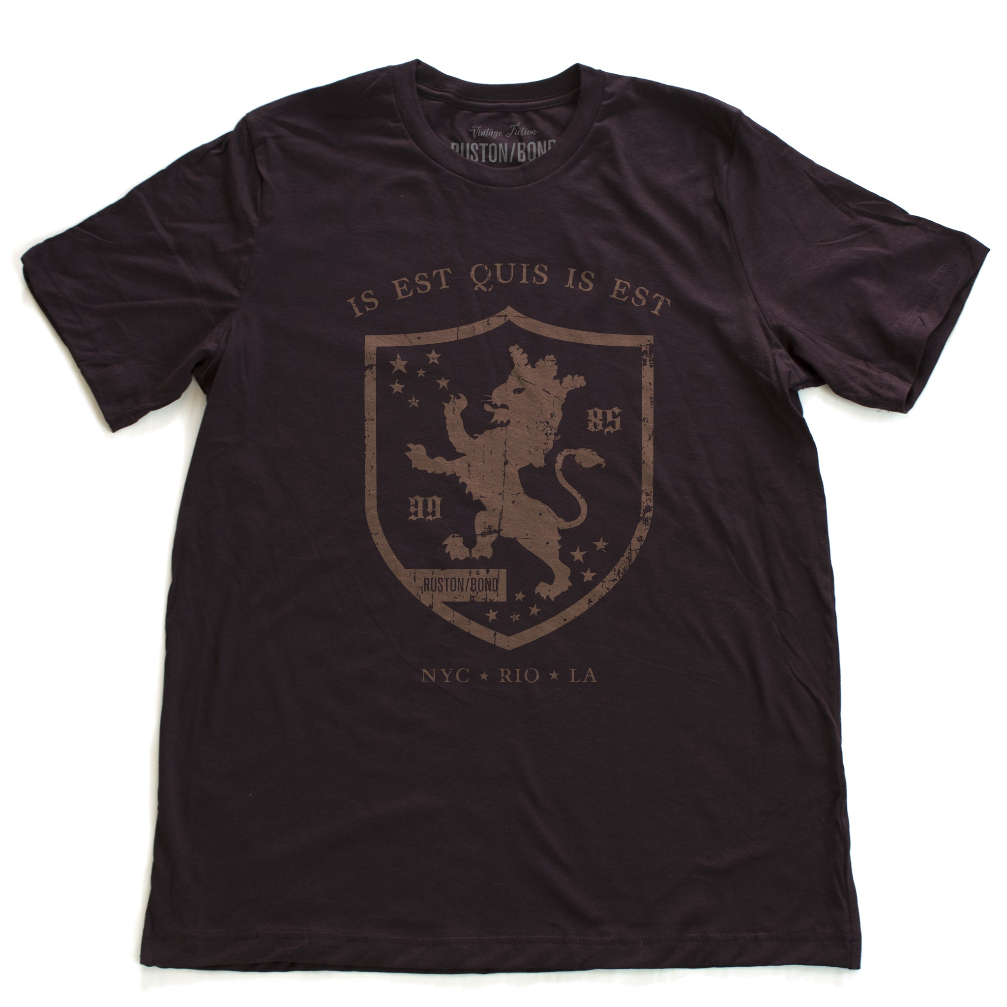 "A retro, vintage-inspired fashion t-shirt in Oxblood, with an medieval graphic of a lion within a shield,surrounded by the sarcastic text in Latin ""it is what it is,"" and New York, Rio, Los Angeles at the bottom. By fashion brand Ruston/Bond, from wolfsaint.net"
