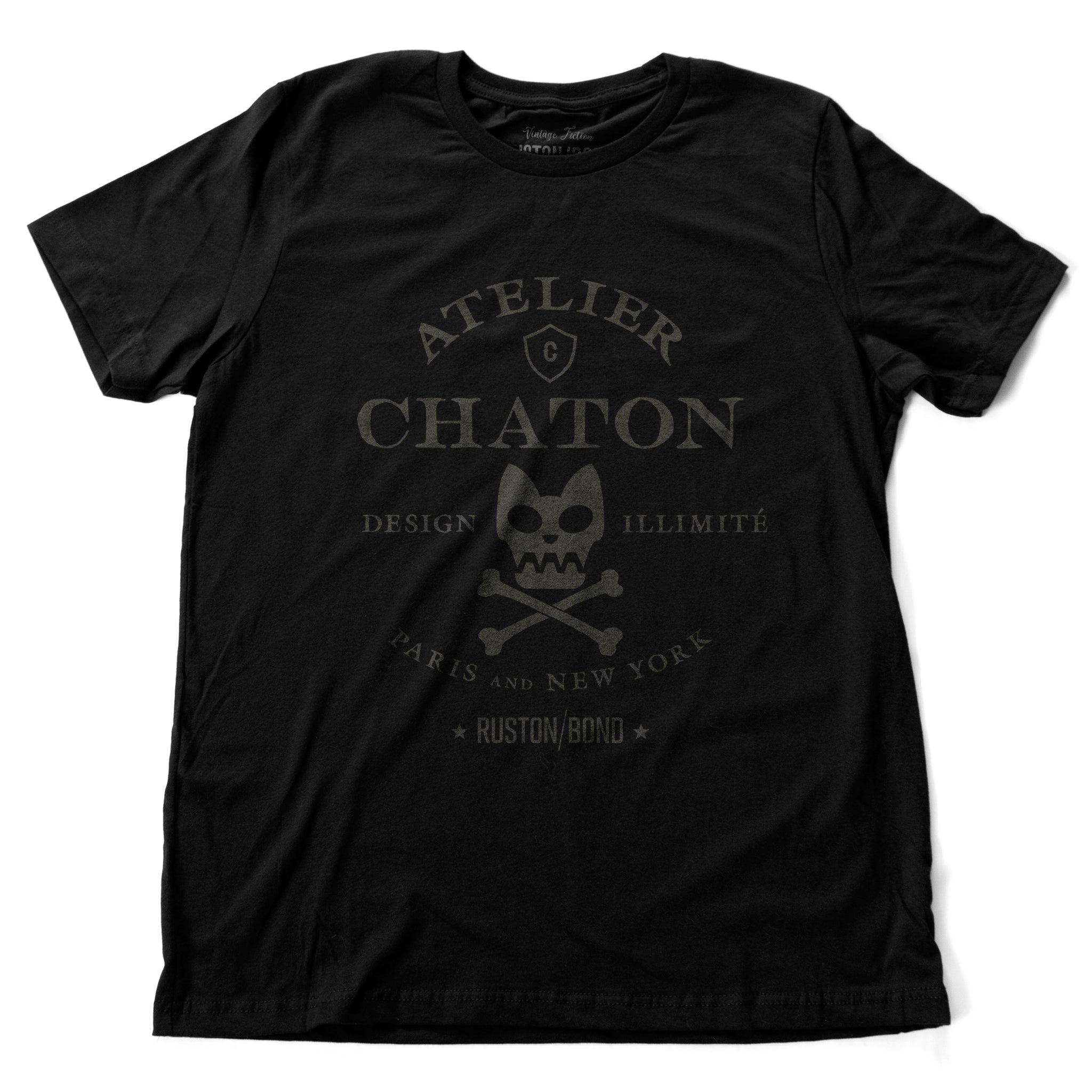 Black retro, vintage-inspired fashion t-shirt for a fictional graphic design studio in Paris and New York, featuring a graphic of a cat skull and cross bones, from brand Ruston/Bond