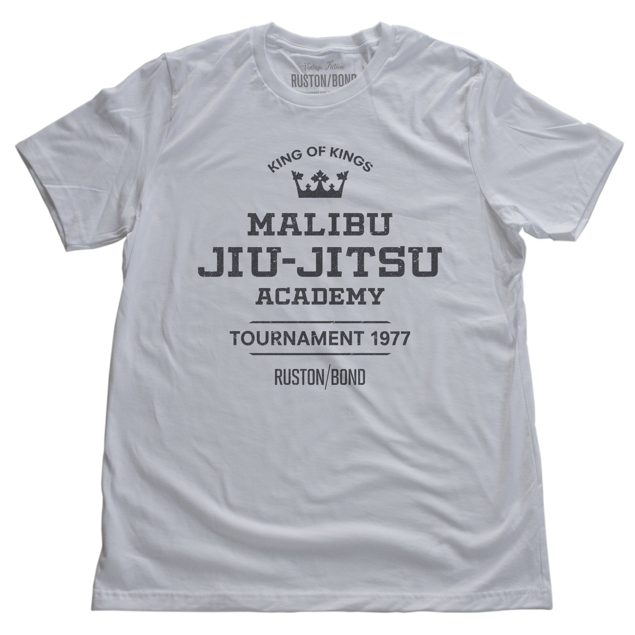 A fashionable, vintage-inspired retro t-shirt in White, featuring a graphic commemorating a sarcastic and fictitious Malibu (California) Jiu Jitsu academy and a 1977 tournament. By fashion brand Ruston/Bond, from wolfsaint.net
