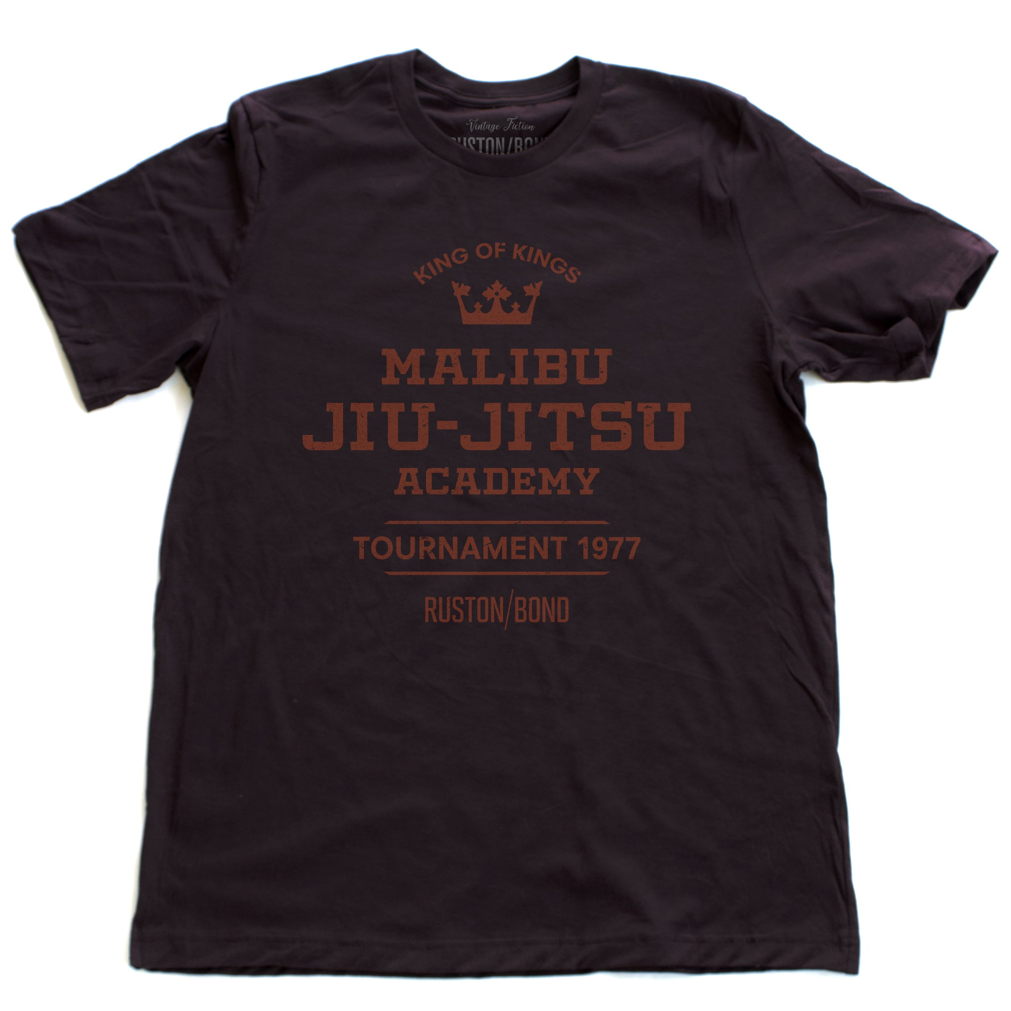 A fashionable, vintage-inspired retro t-shirt in Oxblood, featuring a graphic commemorating a sarcastic and fictitious Malibu (California) Jiu Jitsu academy and a 1977 tournament. By fashion brand Ruston/Bond, from wolfsaint.net