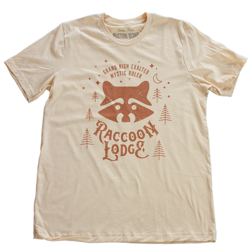 A vintage-look, retro t-shirt in Soft Cream, inspired by Ralph Kramden and Ed Norton's club on The Honeymooners tv show. The graphic depicts the Raccoon Lodge from the tv show. By fashion brand Ruston/Bond, for wolfsaint.net