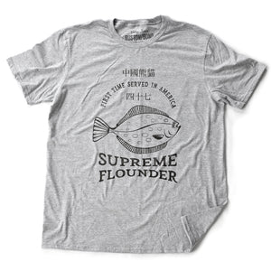 A fashionable retro design t-shirt, inspired by a Seinfeld tv episode, and Julia Louis-Dreyfus' Elaine Benes' character's favorite Chinese food dish. The graphic is a fish, with the words SUPREME FLOUNDER, First Time Served in America, and Chinese characters. From fashion brand RUSTON/BOND for wolfsaint.net