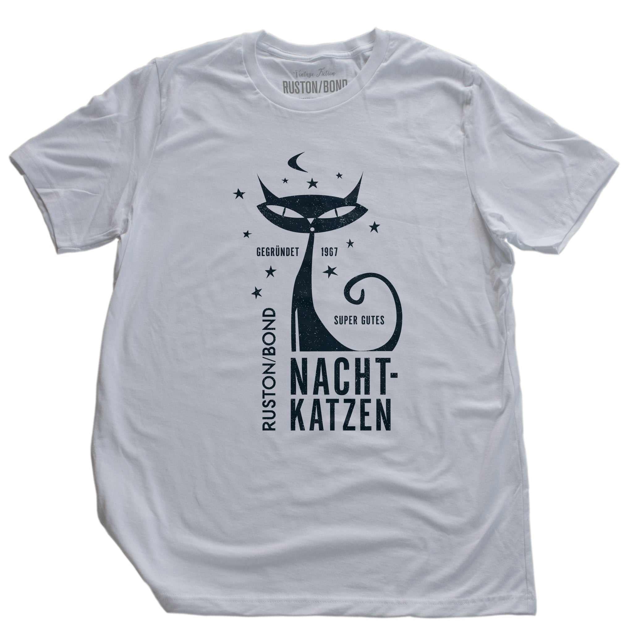 "A vintage-inspired retro design t-shirt in classic White, featuring the image of a stylized cat graphic among stars, and the German text ""NACHTKATZEN, Super Gutes"" — translating to ""Night Cats, super good"" and the year 1967, with the Ruston/Bond logo beneath. From wolfsaint.net"