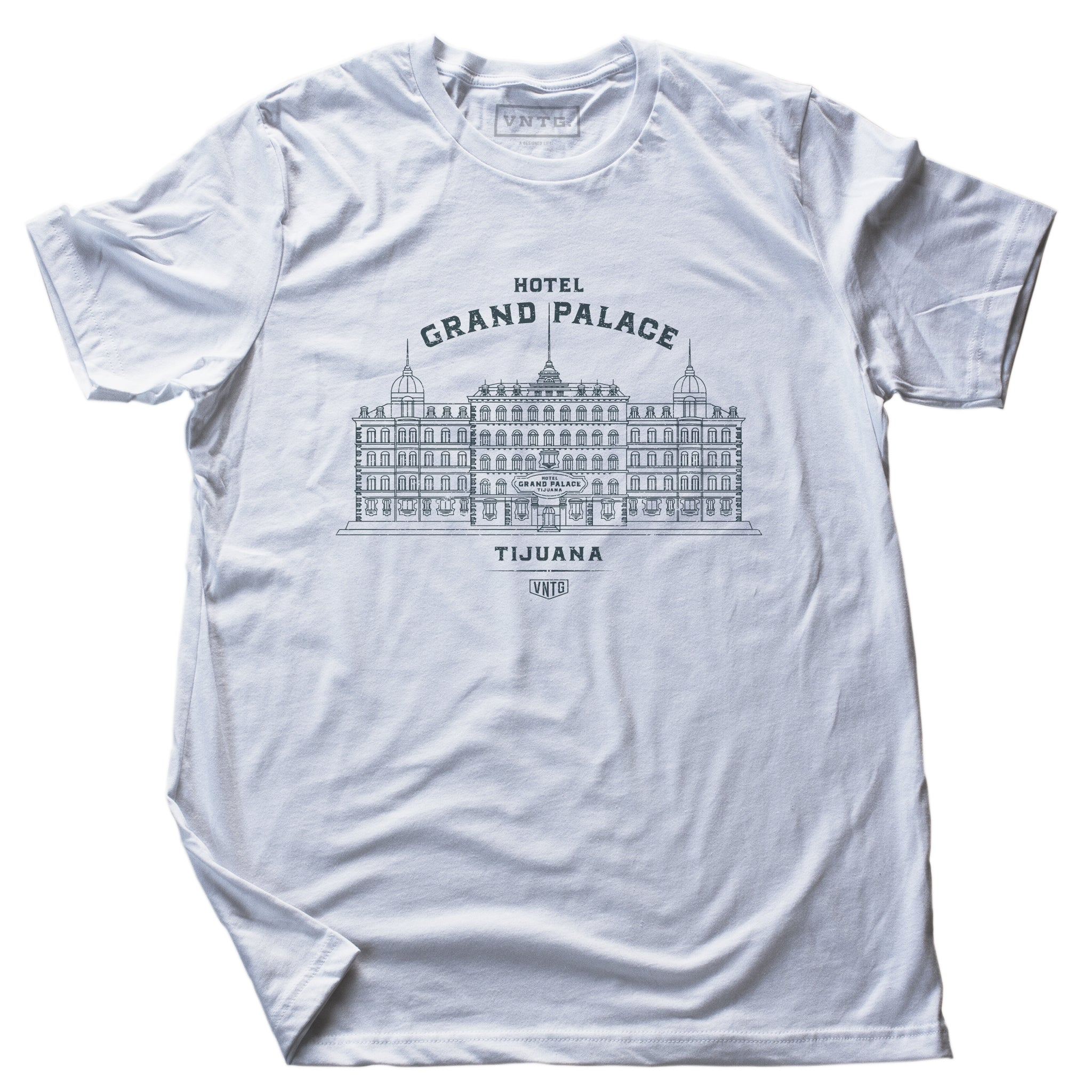 A vintage-inspired retro t-shirt in white, promoting a fictional, sarcastic grand hotel in Tijuana, Mexico. From fashion brand VNTG, from wolfsaint.net The shirt depicts an elegant old hotel in an intricate line drawing. Inspired by the films of Wes Anderson, including The Grand Budapest Hotel.