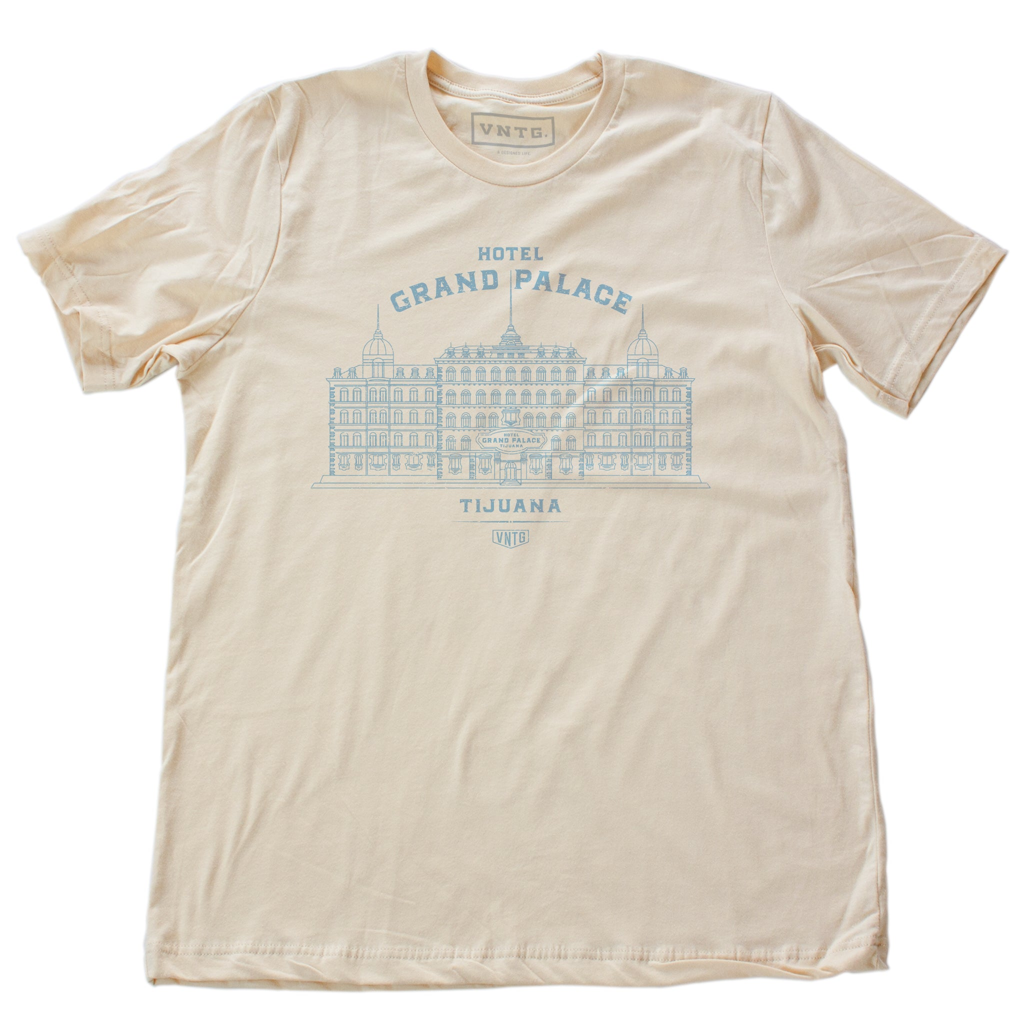 A vintage-inspired retro t-shirt in Soft Cream, promoting a fictional, sarcastic grand hotel in Tijuana, Mexico. From fashion brand VNTG, from wolfsaint.net The shirt depicts an elegant old hotel in an intricate line drawing. Inspired by the films of Wes Anderson, including The Grand Budapest Hotel.