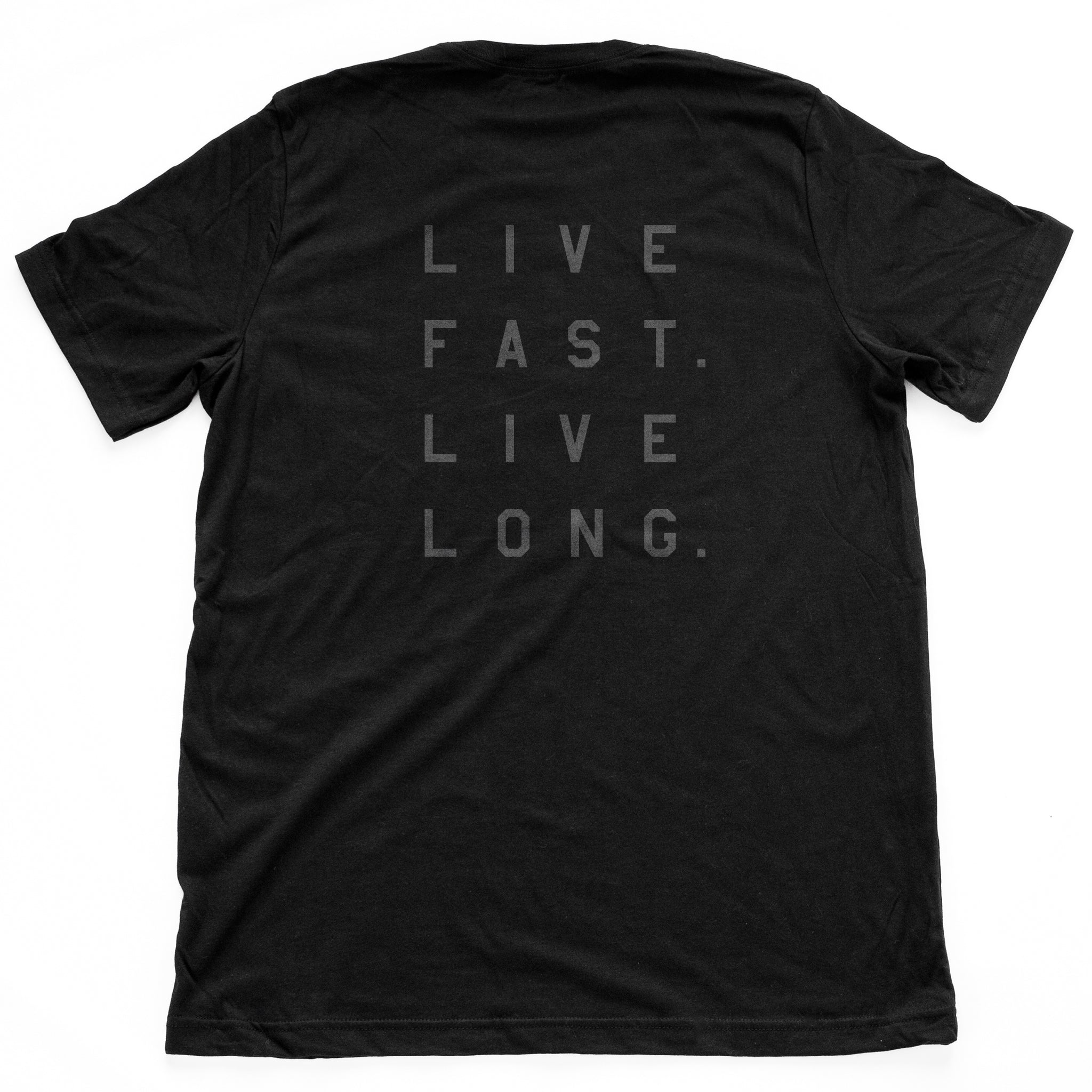 "The back of a classic fashion t-shirt in black, with retro lightning bolt graphic and the Wolfsaint script logo on the front, and bold typography ""Live fast. Live long"" on the back. From wolfsaint.net"