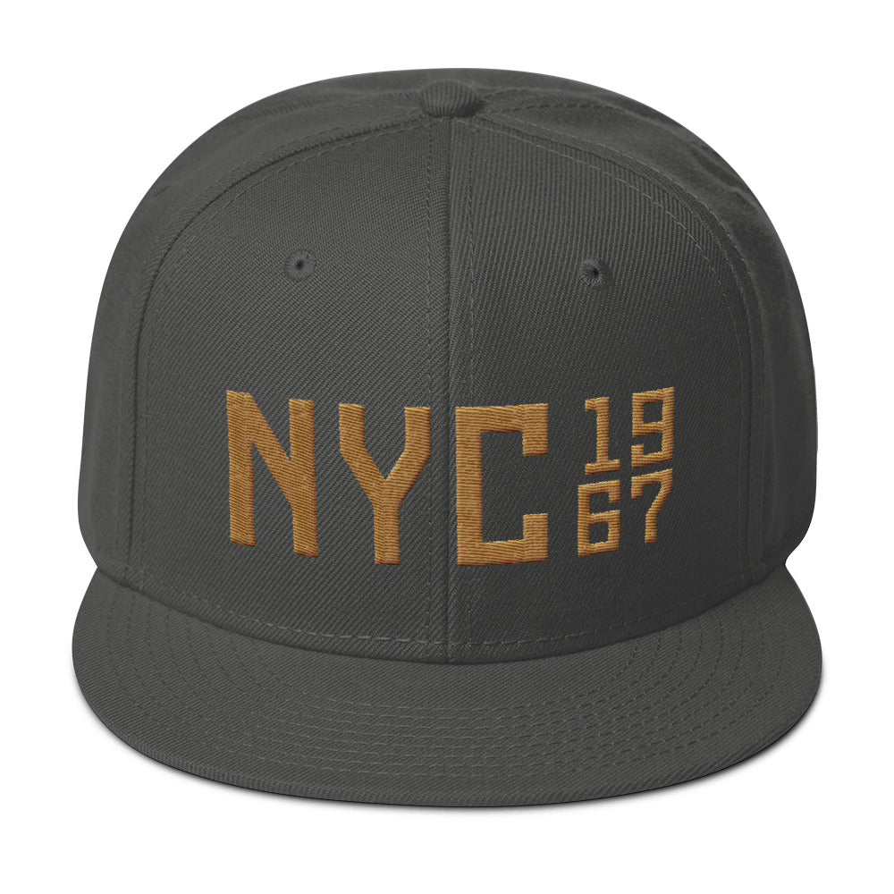 "A puff embroidery high-profile SnapBack cap in Gray with Gold thread of a large ""NYC"" (New York City) with the vintage year 1967 in a stack to the side. From wolfsaint.net"